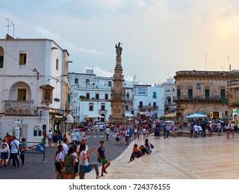 Ostuni, Italy - August 12, 2017. Tourists in Piazza della Liberta square of Ostuni, La Citta Bianca (The White Town), at sunset with Obelisco Sant'Oronzo obelisk in background. Apulia, Italy.