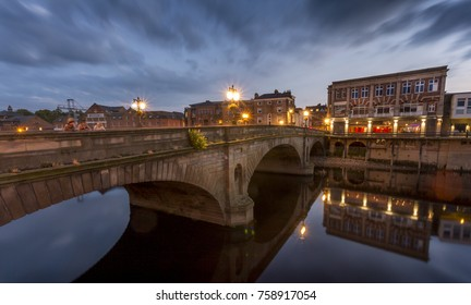 Osue bridge over the river ouse in York England at dusk when the light have come on making reflections in the river.