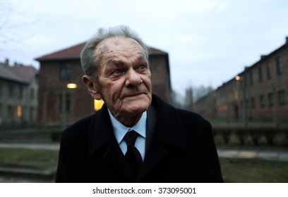 OSWIECIM, POLAND - JANUARY 27, 2016:  Jacek Zieliniewicz an Auschwitz Survivor passes by the main camp gate as he returns to Auschwitz for 71th anniversary of the Camp liberation
