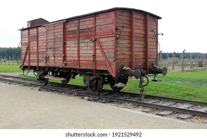 Oswiecim, Poland - June 26, 2012: Infamous railway boxcar, barbed wire fence and barracks in the background, of Auschwitz concentration camp