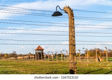 Oswiecim, Poland - October 30,2018: Barbed wire fence with watchtower surrounding concentration camp in Auschwitz Birkenau