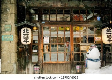 Otaru, Hokkaido, Japan, February 14 2018 : Front of vintage and ancient Japanese restaurant with snowman doll in snowing winter. Otaru in winter was named city of love and destination of couples.