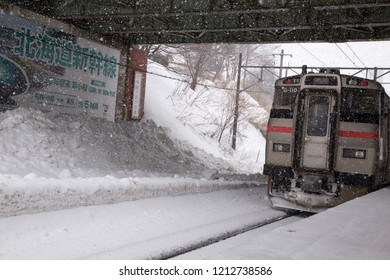 Otaru, Hokkaido, Japan - February 2018 : Departing train from Otaru station while snowing with Snow rail track and train in Otaru city Hokkaido Japan on mid Winter.