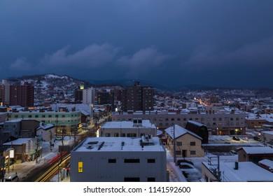 Otaru, Hokkaido, Japan-December 24, 2017: Panorama Cityscape night view of the Otaru city during cloudy morning and winter season, with roof building covered by snow in Otaru, Hokkaido, Japan
