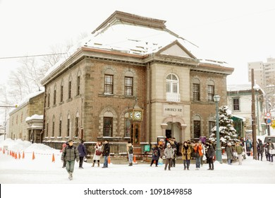 Otaru, Hokkaido prefecture, Japan, February 14 2018 : Music box museum building in heavy snowing day. Although snow is heavy people and tourists are also visiting Otaru music box museum a lot.