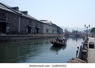 Otaru, Japan - April 20, 2018: A sightseeing boat travels on the Otaru Canal at sunset, Otaru, Japan