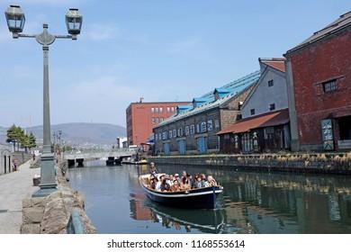 Otaru, Japan - April 21, 2018: A sightseeing boat travels on the Otaru Canal at daytime, Otaru, Japan