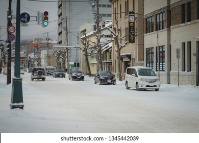 OTARU JAPAN - December 9  : Winter scenery in Otaru city with many passenger cars on the road with traffic and snow on daytime on the winter season at downtown of Otaru. Otaru is a small harbor city.