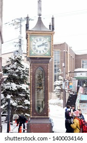 Otaru, Japan, February 14, 2018 : Closeup steam clock tower of Otaru music box museum with tourists on heavy snow day. This steam clock tower which is a souvenir that Vancouver has given to Otaru.