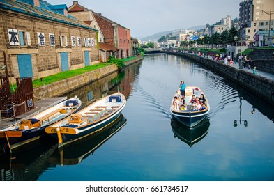 OTARU, JAPAN - JUNE 10, 2017 :Otaru canal with tourist city cruises and boats in a evening day with old building city is landmark of Otaru,Hokkaido,Japan