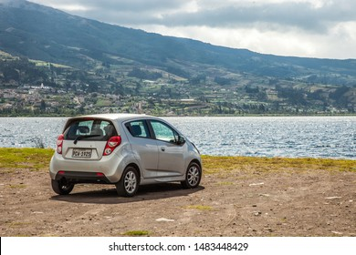OTAVALO, ECUADOR - 12 JANUARY 2019: Vehicle, Chevrolet Spark, parked on the shores of Lake San Pablo in Otavalo, overlooking a large landscape composed of a sky, mountain and water.