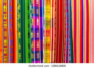 OTAVALO, ECUADOR - APRIL 6, 2019: Colorful Andes textiles on the art and craft market of Otavalo, north of Quito, in Ecuador. These traditional fabrics can also be found in Peru and Bolivia.