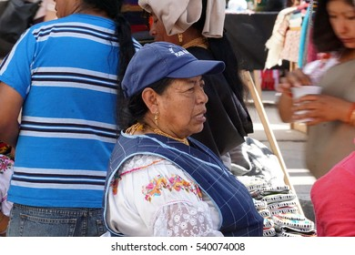 OTAVALO, ECUADOR - AUGUST 13, 2016: Local woman in traditional dress with a blue market vest over it at the handicraft market