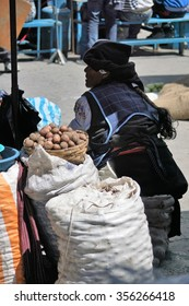 OTAVALO, ECUADOR - DECEMBER 11, 2015: Quechua woman in shadow with her back turned selling potatoes in the market