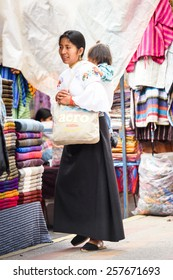 OTAVALO, ECUADOR - JAN 3, 2015: Unidentified Ecuadorian woman carries her little baby at the Otavalo Market. 71,9% of Ecuadorian people belong to the Mestizo ethnic group