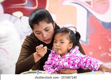 OTAVALO, ECUADOR - JAN 3, 2015: Unidentified Ecuadorian mother and her daughter at the Otavalo Market. 71,9% of Ecuadorian people belong to the Mestizo ethnic group