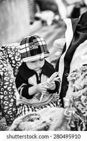 OTAVALO, ECUADOR - JAN 3, 2015: Unidentified Ecuadorian little boy with peas at the Otavalo Market. 71,9% of Ecuadorian people belong to the Mestizo ethnic group