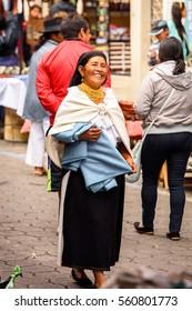 OTAVALO, ECUADOR - JAN 3, 2015: Unidentified Ecuadorian woman in traditional clothes works at the Otavalo Market. 71,9% of Ecuadorian people belong to the Mestizo ethnic group