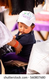 OTAVALO, ECUADOR - JAN 3, 2015: Unidentified Ecuadorian little girl at the Otavalo Market. 71,9% of Ecuadorian people belong to the Mestizo ethnic group