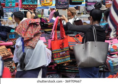OTAVALO, ECUADOR - JANUARY 9, 2016: Woman in traditional quechua dress in the market, standing behind a woman in Western clothing browsing through the products