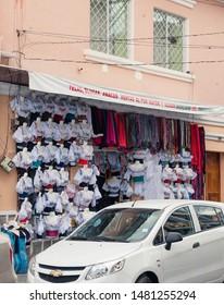 OTAVALO, ECUADOR - JULY 28, 2018: A street vendor selling beautifully designed tops and colorful fabrics on a sidestreet.
