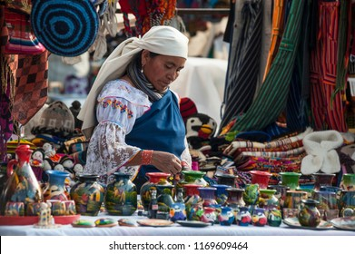 Otavalo, Ecuador - July 5, 2012: Indian women in national clothes sells the products of her weaving, as usual on weekdays on the most famous markets in South America
