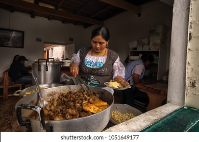 Otavalo, Ecuador- March 17, 2018: indigenous woman preparing a plate of food in a small restaurant