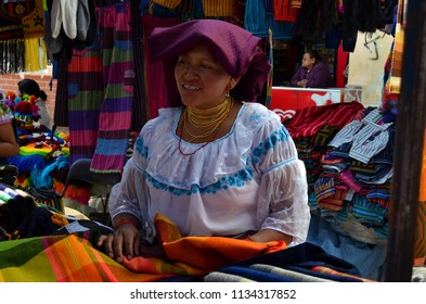 OTAVALO, ECUADOR - OCTOBER 12, 2014 : Otavalo women in traditional clothes sells the handcrafted goods in the market on October 12, 2014 in Otavalo, Ecuador