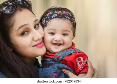 other and daughter hugging and smiling at camera in the park. selective focus, shallow depth of field.