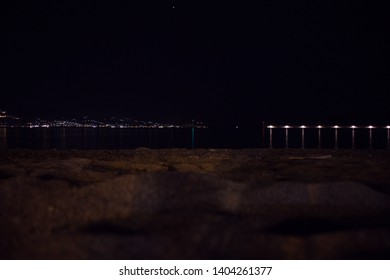 An other view of the beach at night, with lights of the city in background, Kalamata, Greece.