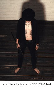 otherworldly world. Man with sword standing on wooden floor barefoot, top view. Warrior in black hat and open clothes showing tattooed torso. Samurai, buddhist concept. Honor and dignity. Harakiri