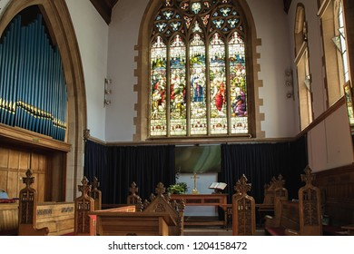 Otley,West Yorkshire,United Kingdom.8.10.2018. Church Organ,stained glass window and wooden seats,All Saints Church.