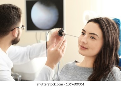 Otolaryngologist examining woman's ear with ENT telescope in hospital