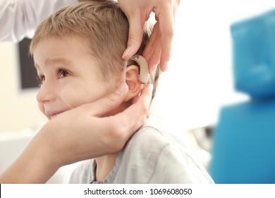 Otolaryngologist putting hearing aid in little boy's ear indoors