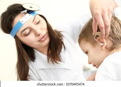 Otolaryngologist putting hearing aid in little boy's ear on light background