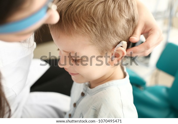 Otolaryngologist putting hearing aid in little boy's ear indoors