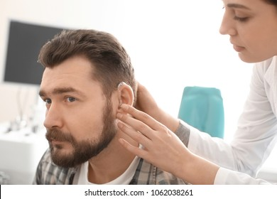Otolaryngologist putting hearing aid in man's ear in hospital
