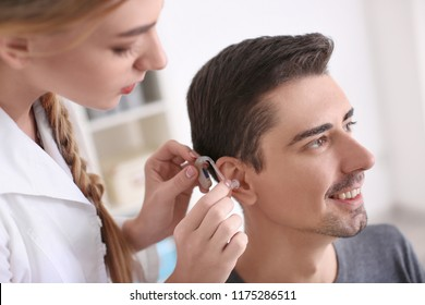 Otolaryngologist putting hearing aid in patient's ear in hospital