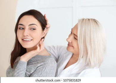 Otolaryngologist putting hearing aid in woman's ear on light background
