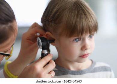 Otorhinolaryngologin untersucht das Ohr eines kleinen Mädchens mit Otoskop. Adenoiditis als Ursache der Otitis media bei Kindern Konzept.