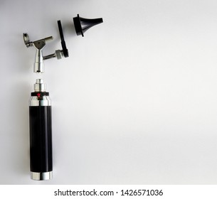 Otoscope for ENT doctor exam ear on pieces disassembly with copy space on white background