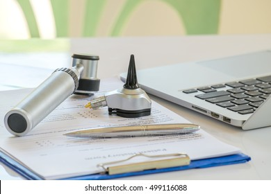 An otoscope and notebook on white table