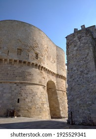 Otranto, Puglia, Italy, February 18, 2020: Tower of Alfonsin, consisting of two semi-towers, and between them is the main gate of the Aragon city, near part of the fortress wall.