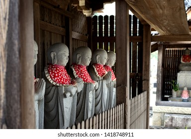 OTSU, JAPAN - JUNE 6, 1019: Stone jizo statues with red aprons at Jobonji—Jobon Temple—in Otsu, Shiga, Japan. Jobonji is a local Buddhist temple that dates from the 13th century.
