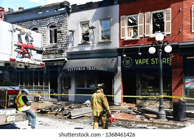 Ottawa, Canada - Apr 13, 2019: Firemen outside restaurant Vittoria Trattoria and adjacent shops which were severely damaged by fire the day before.  Many of the shops on William St  remained closed.
