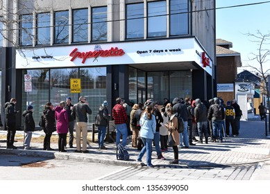 Ottawa, Canada - April 1, 2019: Customers wait in line to enter the mariuana dispensary on the first day for legal retail store sale of cannabis in Ontario.