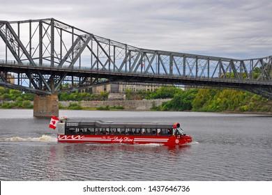 OTTAWA, CANADA - AUG 23, 2011: Lady Dive Tours amphibus on Ottawa River with Alexandra Bridge at the background, Ottawa, Ontario, Canada.