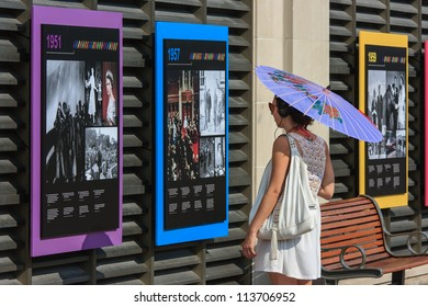 OTTAWA, CANADA - AUGUST 25: A woman reading an outdoor exhibit at the Chateau Laurier Hotel on August 25, 2012 in downtown Ottawa, Ontario. The exhibit was in honor of the Queen's Diamond Jubilee.