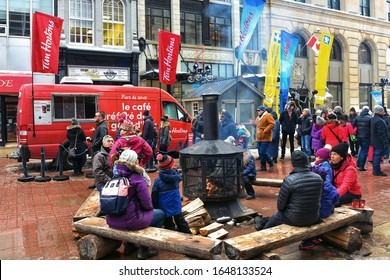 Ottawa, Canada  - February 16, 2020: People sit by the wood fireplace provided for Winterlude Festival near a Tim Horton's van on Sparks Street.
