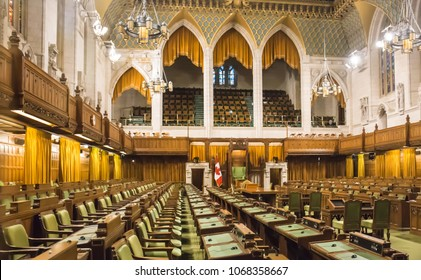OTTAWA, CANADA - JANUARY 4, 2018: Rows of wooden chairs and desks with green leather covers line the House of Commons chamber in the Parliament of Canada.